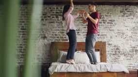 Young husband and wife in casual clothes are jumping and dancing on bed, laughing and having fun in nice loft style stock footage