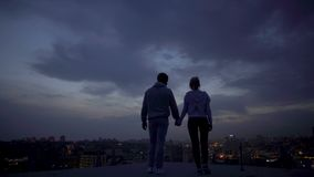 Young husband and wife enjoying moments of solitude, illuminated city at night. Stock footage stock video