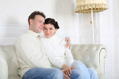 Young husband and wife hug on white leather sofa Stock Photo