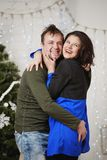 Young husband and wife laugh in Christmas decorate room Royalty Free Stock Photography