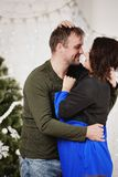 Young husband and wife laugh in Christmas decorate room Royalty Free Stock Images