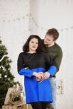Young husband and wife laugh in Christmas decorate room Stock Photos