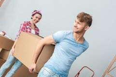 Young couple moving to new place carrying box together talking smiling dreamful stock photos