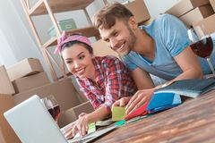 Young couple moving to new place lying drinking wine browsing internet searching for design ideas cheerful stock images