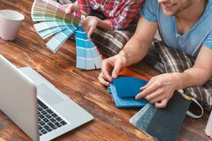 Young couple moving to new place lying using laptop choosing color and flooring close-up happy stock images