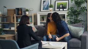 Husband and wife signing agreement taking key from realtor kissing and hugging. Young husband and wife are signing agreement sitting at table and taking key from stock footage