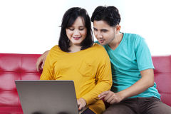 Young husband and wife use laptop on sofa Royalty Free Stock Photos