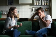 Young husband yawning getting bored listening to excited wife ta. Lking for a long time, tired boyfriend not interested in girlfriend gossiping sitting on couch royalty free stock photography