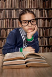 Young hustler with eye glasses or genius in library reading book Royalty Free Stock Photography
