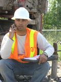 Young Hydrogeologist Field Eng. Ineer is discussing on his cellphone with head office the unusual results from packer test for underground soil layers water flow Royalty Free Stock Photo