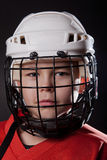 Young ice hockey player on dark background Royalty Free Stock Photo