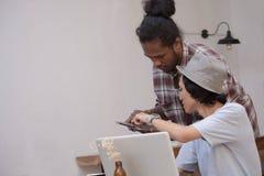 Young idérik man att diskutera med bärbara datorn och minnestavla, ung asiat och svart man som arbetar med minnestavlan och bärba arkivbilder