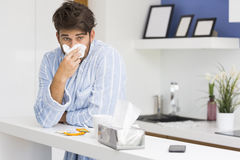 Young ill man blowing nose in tissue paper Stock Image