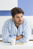 Young ill man with coffee mug and medicine leaning on kitchen counter. Young ill men with coffee mug and medicine leaning on kitchen counter Royalty Free Stock Photo
