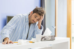 Young ill man with coffee mug, medicine and tissue leaning on kitchen counter Stock Image