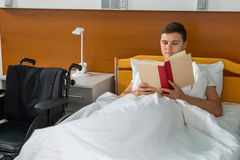 Young ill patient lying in the hospital bed and reading a book i. N hospital ward. Healthcare concept Royalty Free Stock Photos