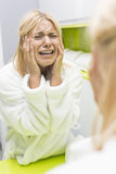 Young ill woman crying while looking at mirrior in bathroom Stock Photos