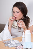 Young ill woman taking pills in her living room Royalty Free Stock Photos