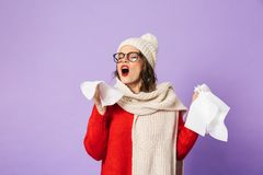 Young ill woman wearing winter hat isolated over purple background holding napkin. Portrait of a young ill woman wearing winter hat isolated over purple royalty free stock images