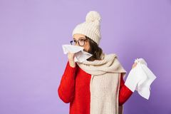 Young ill woman wearing winter hat isolated over purple background holding napkin stock photo