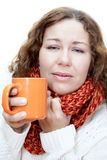 Young illness woman drinks tea with wrapping scarf on neck Royalty Free Stock Image