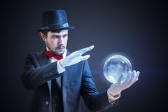 Young illusionist is predicting future and fortune telling from magical ball royalty free stock images