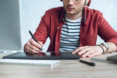 Young illustrator sitting by table. With graphic tablet stock photo