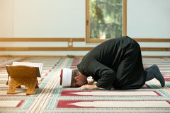 Young Imam praying inside of beautiful mosque royalty free stock photo