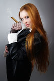 Young impudent woman with red hair  with a cigar Stock Image