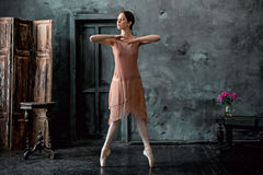 Young and incredibly beautiful ballerina is posing and dancing in a black studio Stock Photography