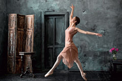 Young and incredibly beautiful ballerina is posing and dancing in a black studio. Young and incredibly beautiful ballerina is posing and dancing in a black Royalty Free Stock Photos