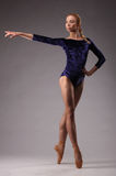 Young and incredibly beautiful ballerina is posing and dancing in studio. Ballerina in blue outfit posing on toes, studio background Royalty Free Stock Photos