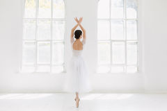 Young and incredibly beautiful ballerina is posing and dancing in a white studio royalty free stock images