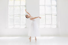 Young and incredibly beautiful ballerina is posing and dancing in a white studio. Full of light Royalty Free Stock Images