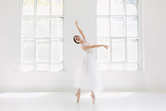 Young and incredibly beautiful ballerina is posing and dancing in a white studio royalty free stock image