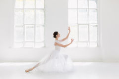 Young and incredibly beautiful ballerina is posing and dancing in a white studio Stock Photo
