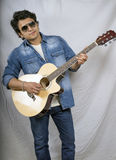 Young indian boy in blue jeans and playing guitar Stock Images