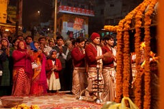 Young indian brahmins in the crowd of people make. VARANASI: Young indian brahmins in the crowd of people make the night ritual dedicated to River Ganges Stock Photos