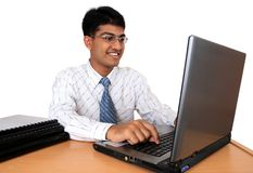 Young Indian business man. Working at his desk in a happy mood (Series Royalty Free Stock Photography