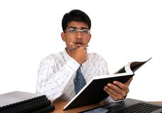 Young Indian business man. Working at his desk. Has a puzzled look.(Series Stock Image