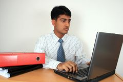 Young Indian business man. Young Indian business man working at his desk. Has a puzzled look.(Series Stock Photos