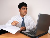 Young Indian business man. Young Indian business man working at his desk. Has a puzzled look.(Series Stock Photo