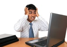 Young Indian business man. Young Indian business man working at his desk. Has a puzzled look.(Series Stock Image