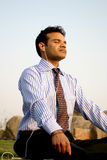Young indian business man meditating. Smiling young indian businessman meditating while listening to music on mp3 player Royalty Free Stock Photo