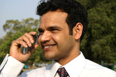 Young Indian business man on mobile. Young Indian business man talking on mobile smiling Royalty Free Stock Photography