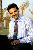 Young indian business man smiling. Smiling young indian businessman working on laptop while listening to music on mp3 player Royalty Free Stock Photos