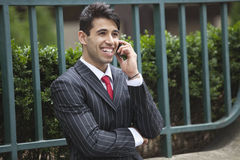 Young Indian businessman on call against fence Stock Images