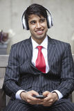 Young Indian businessman listening music on headphones Royalty Free Stock Image