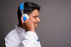 Young Indian Businessman Listening To Music Against Gray Backgro Royalty Free Stock Images