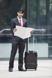 Young Indian businessman with luggage bag reading paper Royalty Free Stock Photos